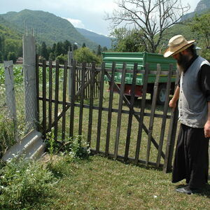 Monk opening a gate for the harvestor to enter